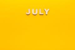 Parola luglio su fondo giallo Fotografia Stock