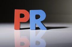 Parola multicolore PR fatto di legno. Fotografie Stock