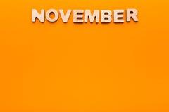Parola novembre su fondo arancio Fotografia Stock Libera da Diritti