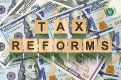 Parola, riforme fiscali composte di lettere sulle particelle elementari di legno contro lo sfondo delle banconote in dollari Affa Immagine Stock Libera da Diritti
