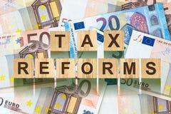 Parola, riforme fiscali composte di lettere sulle particelle elementari di legno contro lo sfondo di euro banconote Affare di con Fotografie Stock Libere da Diritti