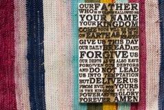 Parola scolpita di legno della preghiera del ` s di signore sui precedenti colorati del tappeto Fotografie Stock Libere da Diritti