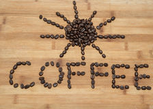 parola scritta e figura del sole fatta dei chicchi di caffè freschi su vecchio fondo di legno Immagine Stock Libera da Diritti