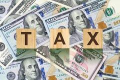 Parola, tassa composta di lettere sulle particelle elementari di legno contro lo sfondo delle banconote in dollari Affare di conc Fotografia Stock
