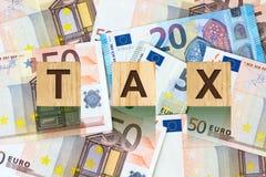 Parola, tassa composta di lettere sulle particelle elementari di legno contro lo sfondo di euro banconote Affare di concetto, fin Immagini Stock Libere da Diritti