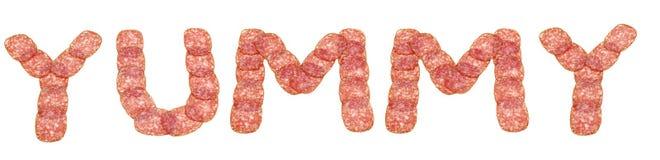 Parola Yummy fatta da salame fotografia stock