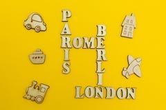 """Parole incrociate dei nomi delle città: """"Parigi, Londra, Berlino, Roma """"su un fondo giallo Figure di legno di un aeroplano, un tr immagini stock libere da diritti"""