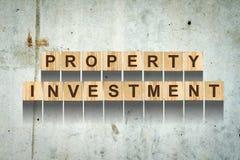 Parole, investimento della proprietà, consistente delle lettere sui cubi di legno per costruzione sui precedenti di vecchio muro  immagine stock