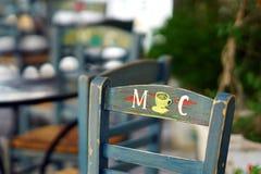 PAROS, ГРЕЦИЯ, деталь 18 2018 деревянных стульев различных цветов в баре в Parikia стоковое изображение