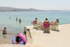Paros, Grécia, o 10 de agosto de 2015 Povos locais e turistas que apreciam suas férias na praia de Arodo na ilha de Paros Fotografia de Stock