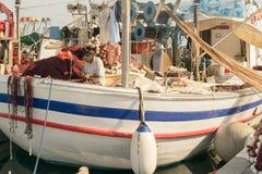 Paros, Grecia 15 agosto 2015 Pescatore su una barca che ripara la rete da pesca all'isola di Paros in Grecia Immagine Stock Libera da Diritti