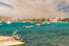 Paros, Grecia 1 de agosto de 2016 Sirva la fijación de la red de pesca en la playa de Alyki en la isla de Paros en Grecia Imagen de archivo libre de regalías