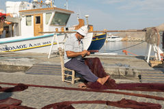 Paros, Greece 15 August 2015. Fisherman repairing the net at Paros island in Greece. Royalty Free Stock Images