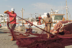 Paros, Greece 15 August 2015. Fishermen on their everyday work repairing the fishing net at Paros island in Greece. Royalty Free Stock Photography