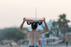 Paros, Greece. 09 August 2015. Surfer with the surf on his head going to chase the waves. Stock Images