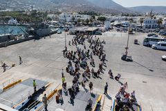 PAROS, GREECE - SEPTEMBER 17, 2016: Passengers and cars embark on a ship at the port of Paros in Greece. Paros is a beautiful Cycladic island visited by many royalty free stock images