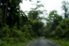 Parque borroso con la luz del bokeh un largo el camino en llover día encendido foto de archivo