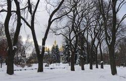 Parque coberto de neve Vladimirskaya Gorka e catedral Dourado-abobadada de Mikhailovsky na distância imagem de stock