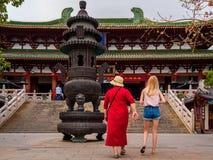 PARQUE CULTURAL de NANSHAN, HAINAN, CHINA - 5 DE MARZO DE 2019 - dos turistas femeninos cauc?sicos en un templo chino foto de archivo libre de regalías