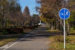 Parque da cidade para andar com bancos e sinal de estrada imagens de stock royalty free