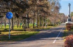 Parque da cidade para andar com bancos e sinal de estrada fotografia de stock royalty free