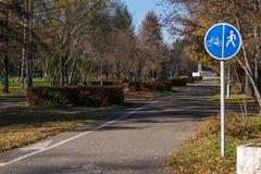Parque da cidade para andar com bancos e sinal de estrada foto de stock