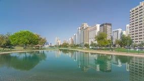 Parque da praia do bulevar de Corniche ao longo do litoral no hyperlapse do timelapse de Abu Dhabi com os arranha-céus no fundo video estoque