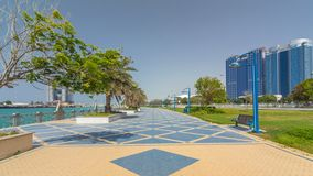Parque da praia do bulevar de Corniche ao longo do litoral no hyperlapse do timelapse de Abu Dhabi com os arranha-céus no fundo vídeos de arquivo