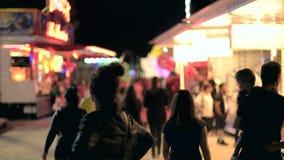 Parque de atracciones en caminar defocused de la gente de la ciudad de la noche metrajes