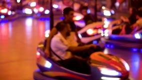 Parque de atracciones en la ciudad de la noche con las porciones de coches de parachoques defocused almacen de video