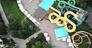 Parque de atracciones La gente monta las diapositivas, nadada en la piscina metrajes