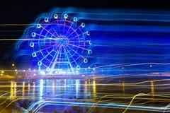 Parque de diversões na noite - fulgor de néon da roda de Ferris no movimento fotografia de stock royalty free