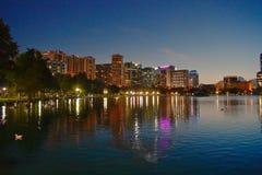 Parque de Eola do lago e construções do centro coloridas no fundo azul da noite fotos de stock