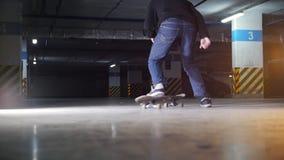 Parque de estacionamento subterrâneo Um skateboarding do homem novo Truque complicado praticando video estoque
