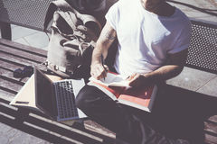 Parque de la ciudad de la camiseta blanca del hombre de la foto del primer y cuaderno de la escritura que se sientan que llevan E Imágenes de archivo libres de regalías
