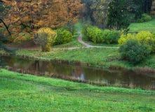 Parque del otoño con un río y trayectorias que caminan en la orilla del río Imágenes de archivo libres de regalías