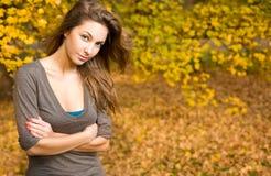 Parque del otoño y un brunette hermoso. Foto de archivo