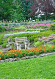 Parque del verano, banco en un jardín, flores, plantas Fotografía de archivo libre de regalías
