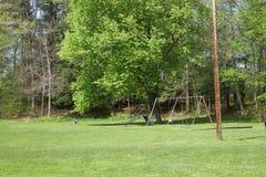 Parque del verano con el swingset Foto de archivo libre de regalías
