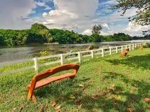 Parque do banco de madeira em público, perto do rio Fotografia de Stock Royalty Free