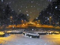 Parque do inverno na noite Queda de neve e lanternas leves alaranjadas fotos de stock