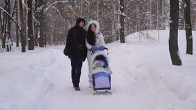 Parque do inverno Os pares passam o tempo com uma criança no parque A mulher no revestimento morno rola o carrinho de criança com vídeos de arquivo