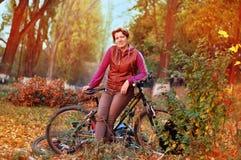 Parque do outono A mulher aprecia montar foto de stock royalty free