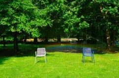 Parque do verão, gramado verde, cadeiras de jardim Fotografia de Stock Royalty Free