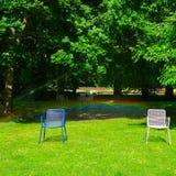 Parque do verão, gramado verde e cadeiras de jardim Foto de Stock Royalty Free