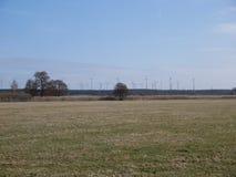 Parque eólico con las turbinas vistas sobre un campo de granja Imágenes de archivo libres de regalías