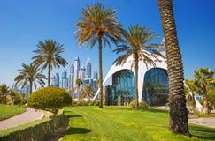 Parque exótico com palmas e os arranha-céus luxuosos do porto de Dubai, Dubai, Emiratos Árabes Unidos Fotografia de Stock