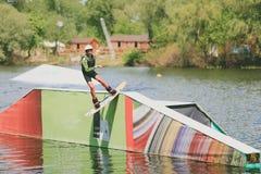 Parque extremo, Kiev, Ucrania - pueden, 07, 2017 - un salto practicado del hombre joven en Wakeboarding Foto que procesa el grano Foto de archivo