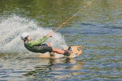 Parque extremo, Kiev, Ucrania - pueden, 07, 2017 - un salto practicado del hombre joven en Wakeboarding Foto que procesa el grano Fotografía de archivo