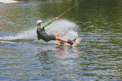 Parque extremo, Kiev, Ucrania - pueden, 07, 2017 - un salto practicado del hombre joven en Wakeboarding Foto que procesa el grano Fotografía de archivo libre de regalías